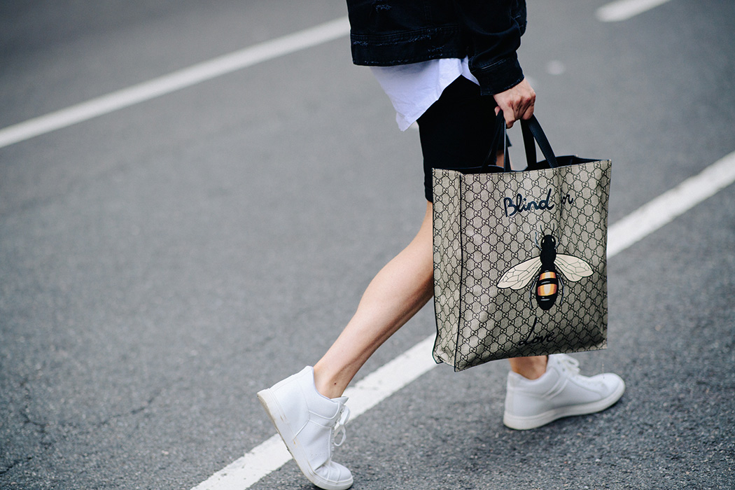 Man wearing Gucci bag and white sneakers